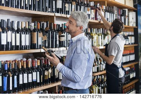Customer And Salesman Choosing Wine Bottles In Store