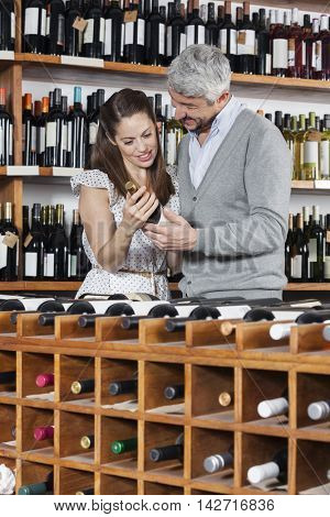 Couple With Wine Bottle Standing At Rack