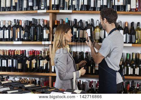 Salesman Assisting Female Customer With Wine