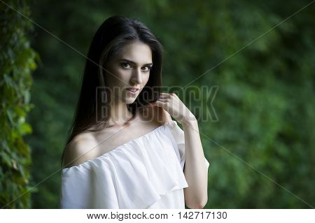 Portrait of a beautiful happy smiling caucasian woman in white dress with open shoulders clean skin long hair and casual makeup nature background