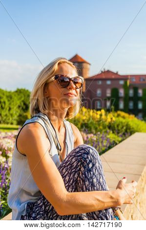 Female traveler sitting and enjoys the view of Wawel Castle on the background of Sandomierz Watchtower and former barracks. Krakow, Poland