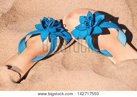 Blue flipflops on sand in sunny day