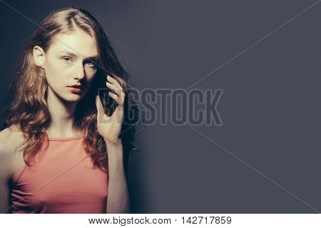 Young woman with curly brown hair pretty serious face attractive makeup in red top posing with her hand near face on dark background studio copyspace