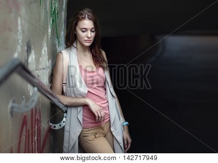 Young beautiful sad teen in urban background