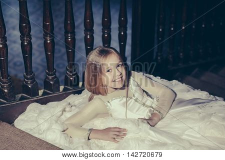 Small Girl Sitting On Wooden Stairs