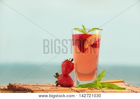 Glass of strawberry lemonade with pieces of strawberry, lemon and fresh mint. Closeup of mojito with beach on background. Fresh summer bright strawberry cocktail.