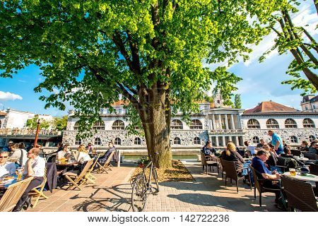 Ljubljana, Slovenia - May 6, 2016: People sit at the cafe near Ljubljanica river in the old city centre in Ljubljana. Ljubljana is the capital of Slovenia and famous european tourist destination.