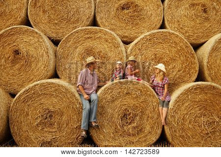 young family on haystacks in cowboy hats