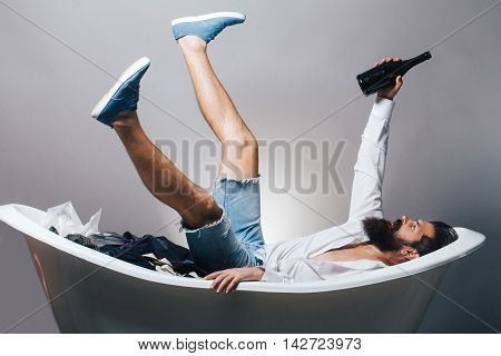 young handsome bearded man with long beard laying drunk in bathtub with wine bottle on grey studio background