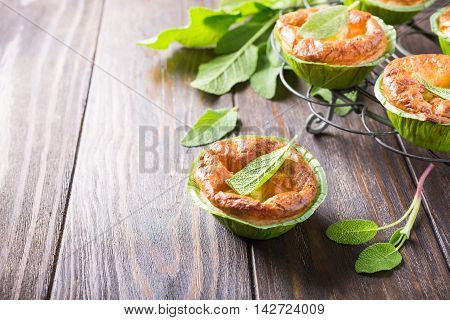 Savory cheddar cheese and leek mini pies with sage on dark wooden table