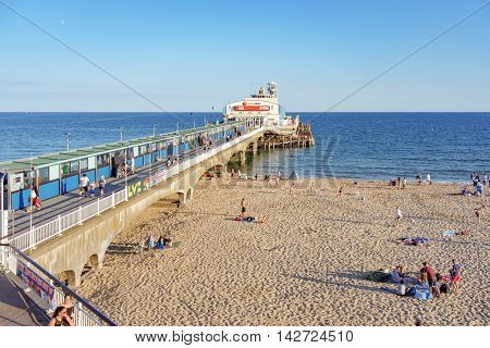 Bournemouth/UK. 14th August 2016. Day trippers enjoy the warm sunshine of Bournemouth Pier and beach at dusk.