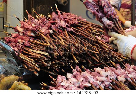 Raw chunks of lamb meat on bamboo skewers waiting to be grilled on the Muslim Food street within the city of Xian in Shaanxi province.
