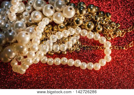 Close up of beautiful creamy and golden pearls against a red glitter. Luxury jewelry background