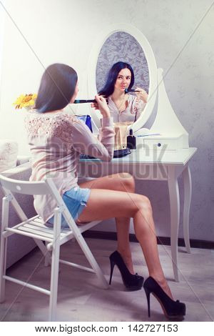 beautiful young lady mirror admires reflexion in the bedroom
