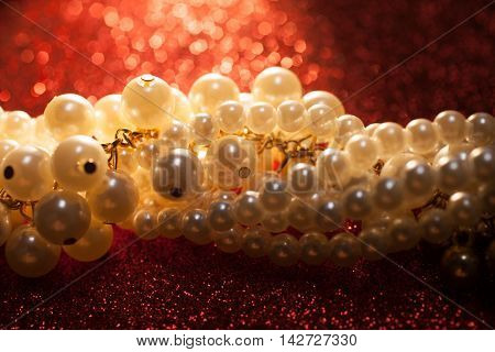 Beautiful creamy pearls against a red glitter. Luxury jewelry background