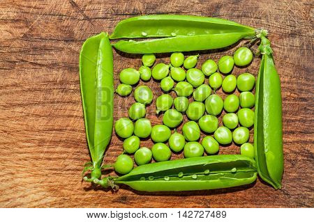 green peas in green frame on the wooden background