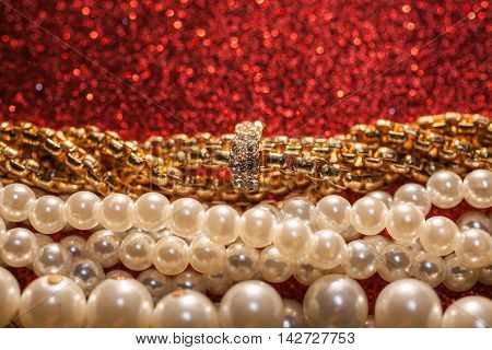Close up of luxury beautiful jewelry on a red glitter background.
