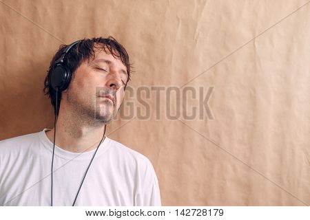 Adult male enjoying listening to favorite music podcast on headphones man with closed eyes leaning onto wall and relaxing.