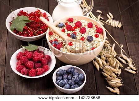 Bowls of oat flakes cereal and various berries.Raspberry, blueberry and redcurrant.