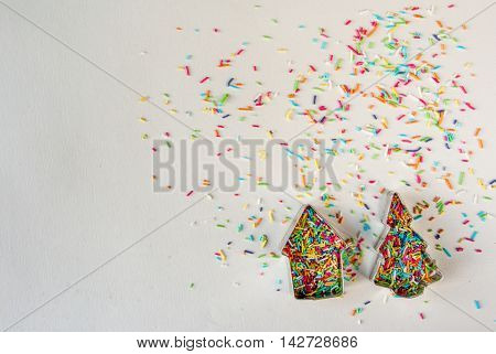 Christmas mood. Cookie cutters for Christmas cookies and colorful sprinkling of cookies on a white background.