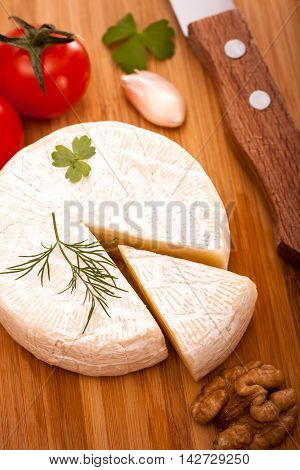 Brie. Sliced soft cheese and knife top view