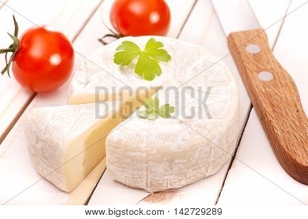 Brie soft cheese and knife on white table