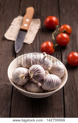 Bowl of chinese solo garlic without cloves, tomatoes and knife on brown wooden background