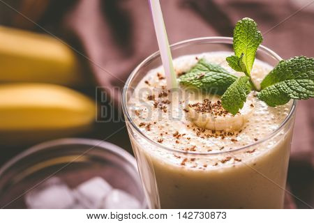 Glass of chocolate banana smoothie with straw closeup shot