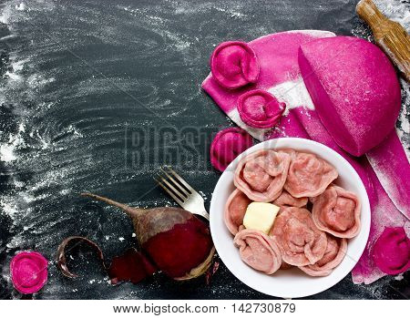 Fresh homemade dough with beetroot juice and pink dumplings stuffed with meat on a black background with ingredients. Making creative and healthy dumplings process top view blank space for text