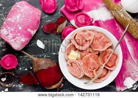 Healthy pink beetroot dumplings or ravioli stuffed with meat. Fresh homemade dough with beetroot juice top view