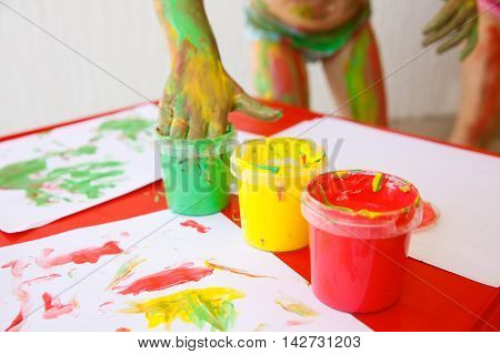 Child dipping fingers in washable non-toxic finger paints painting a drawing. Creativity sensory play innovative learning fun childhood concept.