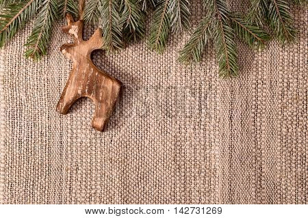 Christmas decoration with fir branch and wooden deer above crafts textile background horizontal