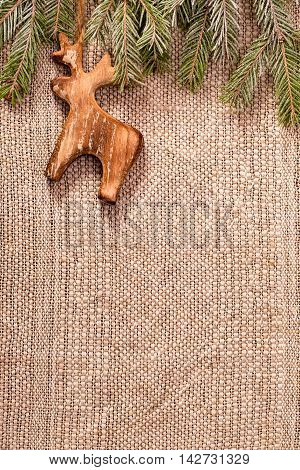 Christmas decoration with fir branch and wooden deer on crafts textile background
