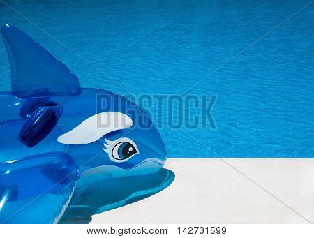 Pool side background shot on a sunny summers day showing an inflatable dolphin resting on a marble stone poolside. room for text or copy space ideal for a banner or poster