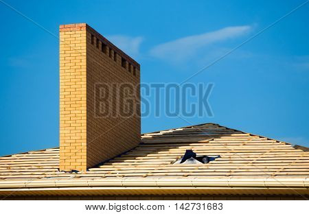 Roof under constructions with lots of tile and yellow brick chimney.