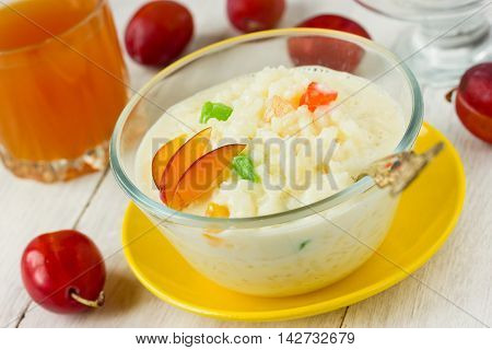 Useful rice milk porridge with fruit and candied fruits on a white background dietary breakfast. Selective focus