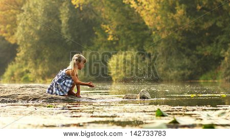 beautiful little girl in nature play near lake