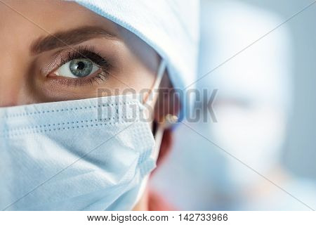 Close up portrait of adult female surgeon doctor wearing protective mask and cap. Half face closeup. Healthcare medical education emergency medical service and surgery concept