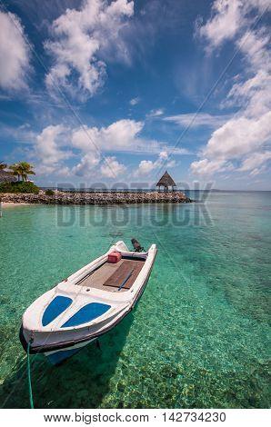 Boat in the shallow tropical lagoon at Maldivian island