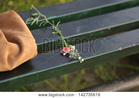 a bunch of wilted wild flowers on a bench next to a bag