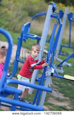 two children playing outdoors with outdoor gym equipment