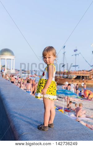 Portrait of a little girl in a yellow dress sitting on the curb with his back to the camera at the public beach