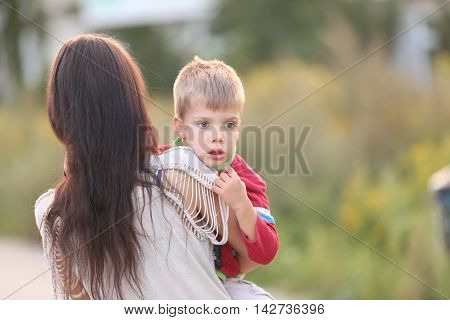 sad little blond boy carried by his mother
