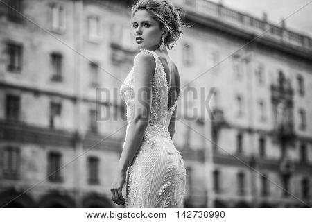 Beautiful girl in the wedding dress on the walk