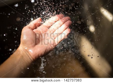 Human hand in sunlight under falling water