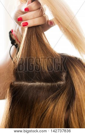 Close up view of hairdresser hand holding strand of hair preparing to cutting and dyeing hair. Haircare making new hairdo keratin restoration and hair therapy concept