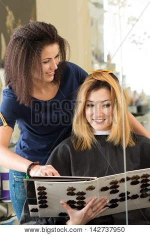 Hairdresser salon visitor looking at book of color samples sitting in front of mirror. Woman at hairstylist office choosing new hair color. Haircare beautician dyeing or changing hair colour concept