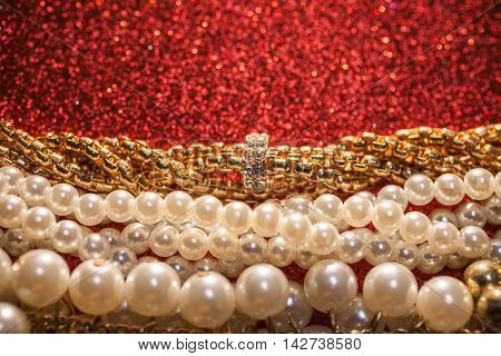 Luxury beautiful pearl necklace on a red glitter background.