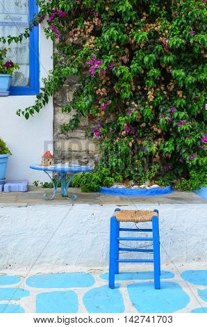 Greek style blue and white resting corner wooden blue chair small round table and flowers