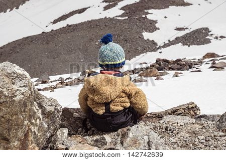 Little child of mountaineers sitting on the rock. Mountain slope. French alps.